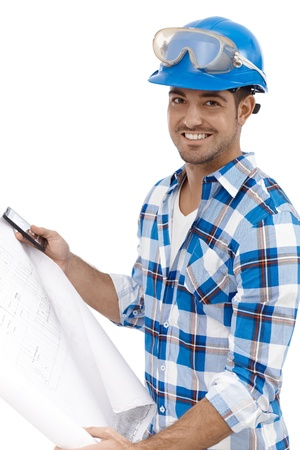 safety googles: Young architect holding floor plan smiling. Stock Photo