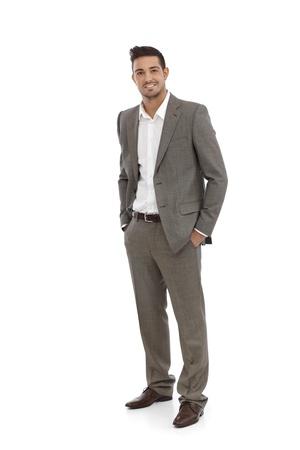 full size: Handsome businessman standing in grey suit, hands in pocket.