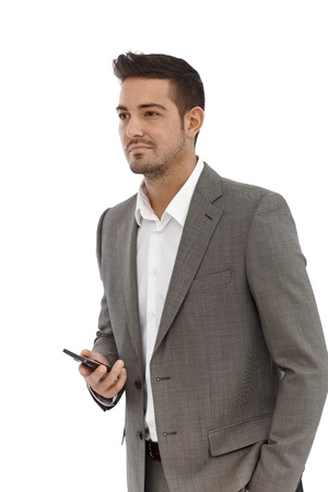 Young businessman holding mobile phone in hand, other hand in pocket. photo