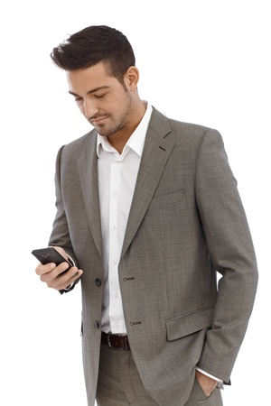 Young businessman using mobilephone, writing text message. photo
