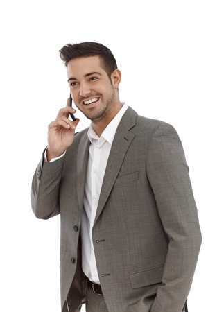 Happy young businessman talking on mobile phone over white background. photo