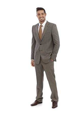 Elegant businessman smiling in grey suit over white background.