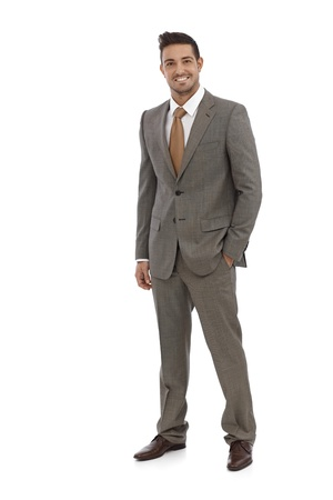 full size: Elegant businessman smiling in grey suit over white background.