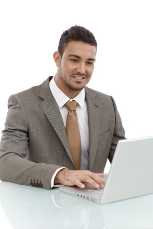 stockphoto: Happy young businessman sitting at desk, working on laptop computer.
