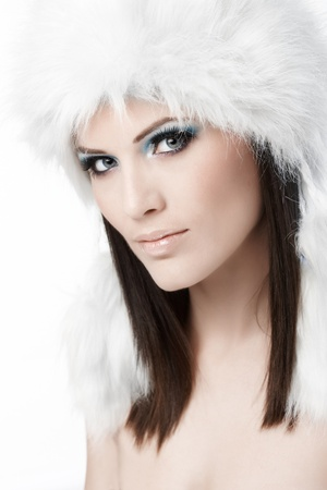 Winter beauty portrait of young attractive woman in fur cap, looking at camera. photo