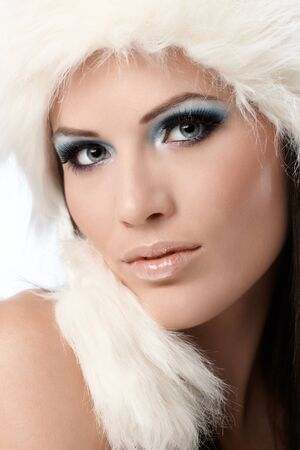 smile close up: Beauty portrait of young woman in white fur cap and professional makeup. Stock Photo