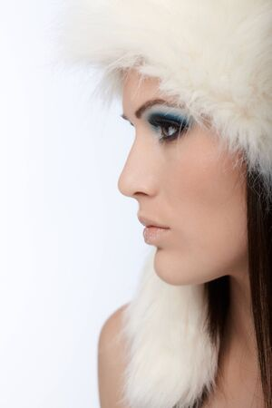 Beautiful female profile in white fur cap and professional makeup. photo