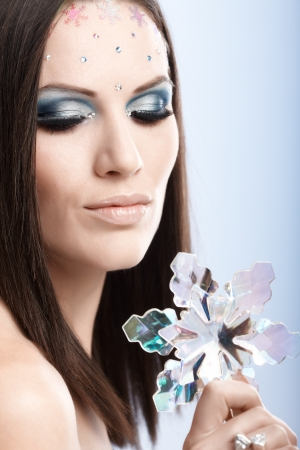 Close-up portrait of winter beauty in fancy makeup with rhinestones and snowflake. photo