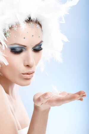 Winter beauty sending a kiss in white feather cap and fancy makeup. photo