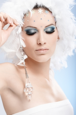 female face closeup: Luxurious winter beauty with crystal jewel and professional makeup with strasses.