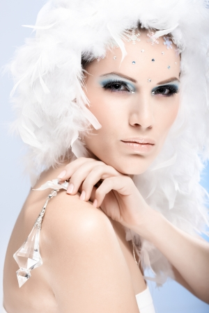 Glamour portrait of winter beauty holding crystal gem, wearing white feather cap and luxurious makeup. photo