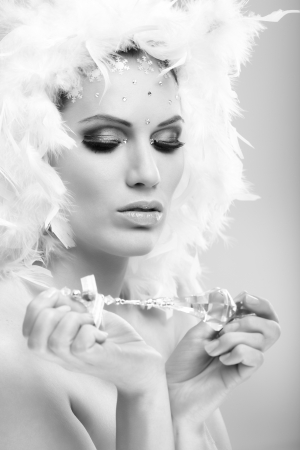 Black and white glamour photo of young winter beauty with professional makeup and crystal gem. photo