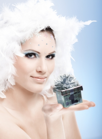make a gift: Attractive winter girl holding small present box, wearing professional makeup with strasses and white feather hat.
