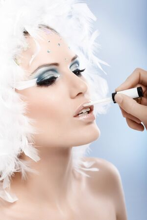 Beautiful model with professional winter makeup, lipstick being applied. photo