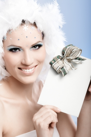 Beautiful woman in winter makeup and white feather cap holding fancy present, smiling. photo