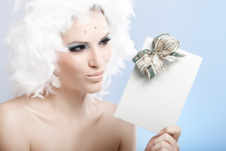 Impish winter beauty in white feather cap and luxurious makeup holding fancy christmas present. photo