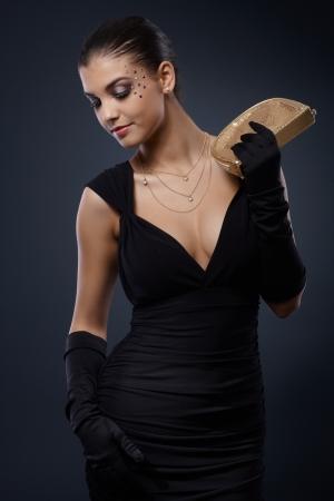 traje de gala: Mujer joven atractiva con maquillaje de fantas�a pedrer�a posando en vestido de noche elegante con el bolso.