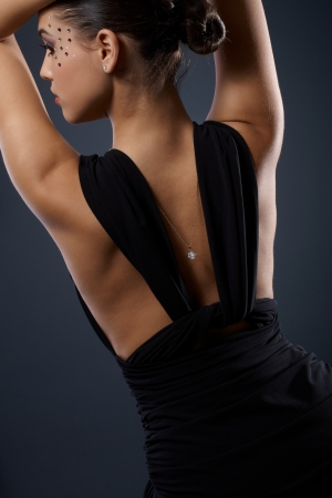 Attractive female back in fancy black dress, side view of beauty face wearing rhinestones makeup, posing with arms raised. photo