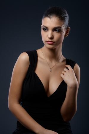 traje de gala: Mujer elegante con maquillaje de fantas�a en el vestido negro de c�ctel seductor. Foto de archivo