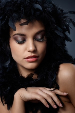 Beauty posing with black feather boa, extravagant eye makeup. photo