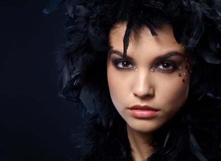 Extreme beauty with rhinestones makeup and wearing black feather boa on head. photo