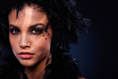 Intense look of beautiful woman wearing party makeup and black feather boa, stripes of shadow and light. photo