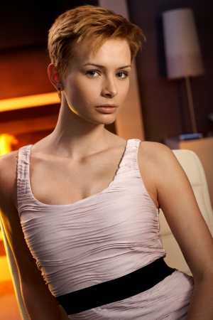 gingerish: Pretty woman sitting in cosy room with mysterious look. Stock Photo