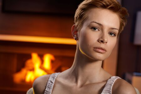 Portrait of seus young woman by fireplace. Stock Photo - 15100751