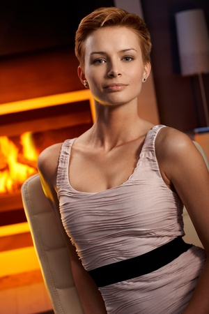 Beautiful young woman sitting by fireplace in cosy room, smiling. Stock Photo - 15100780