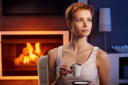 Beautiful young woman having coffee by fireplace in cosy room. photo