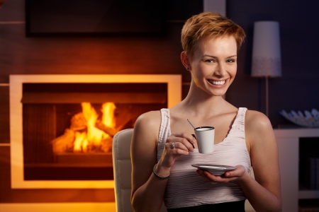 Happy young woman drinking coffee by fireplace in cosy room. Stock Photo - 15100664