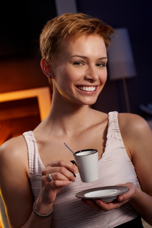 Pretty woman drinking coffee in cosy room, smiling happy. Stock Photo - 15100776