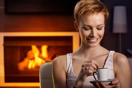Happy woman sitting by fireplace, drinking coffee, enjoying peace. photo