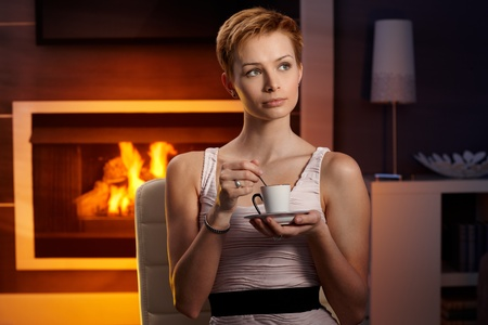 Daydreaming young woman drinking coffee at home by fireplace. photo