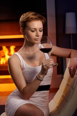 gingerish: Sexy woman sitting in cosy room, enjoying smelling glass of wine.