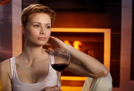 gingerish: Daydreaming woman sitting in cosy room by fireplace, holding a glass of wine, daydreaming.