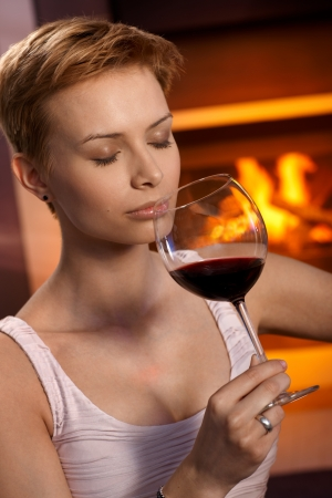 Attractive young woman smelling glass of wine, enjoying drink by fireplace. photo