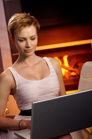 Pretty young female using laptop computer by fireplace. photo