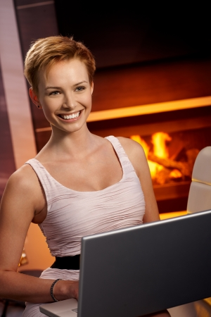 Beautiful young woman using laptop computer at home by fireplace, smiling happy. photo