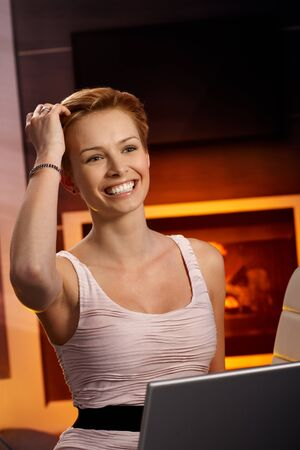 gingerish: Pretty woman browsing internet at home by fireplace, smiling happy, hand in hair.