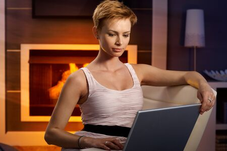 Young woman working with laptop in cosy room by fireplace. photo