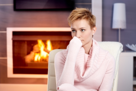 gingerish: Attractive young woman sitting by fireplace at home in pink pullover, thinking.