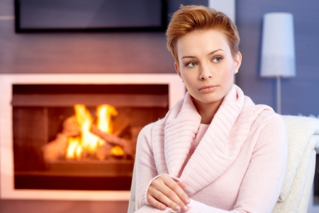 gingerish: Beautiful young woman thinking by fireplace at home.