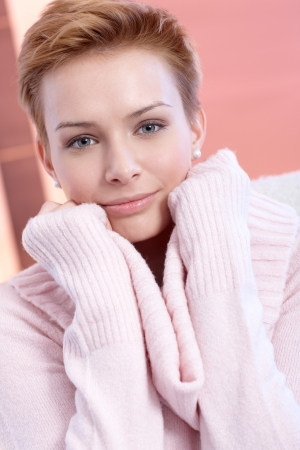 woman short hair: Close-up portrait of smiling young woman in pink.