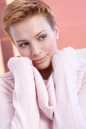 gingerish: Close-up portrait of attractive young woman in pink pullover, looking away. Stock Photo