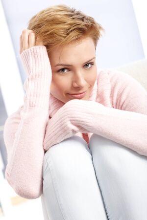 hugging knees: Smiling attractive woman hugging knees, hand in hair.
