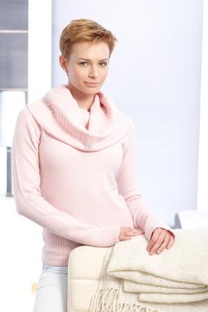 gingerish: Pretty short hair woman standing behind chair at home.