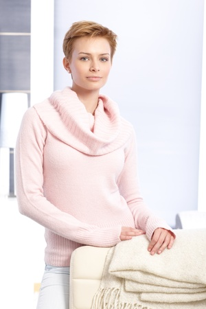 gingerish: Attractive young blonde woman standing at home behind chair, wearing pink pullover.