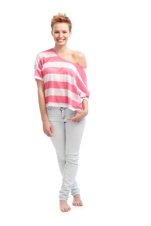 full size: Trendy young woman standing barefoot in t-shirt and jenas, smiling. Stock Photo