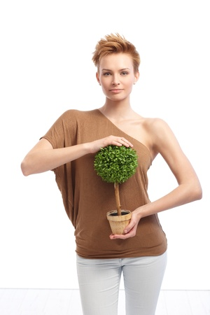 Trendy young woman with short hair holding green potted plant, smiling. photo